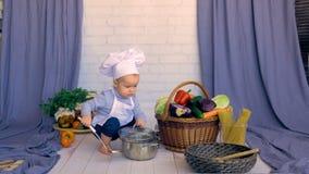 Nettes Babykind, das gesundes Lebensmittel in der Wanne kocht stock video