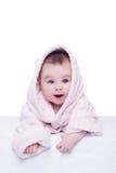 Nettes Babykind im rosa Bademantel, der sich auf Decke hinlegt Lizenzfreies Stockfoto