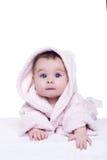 Nettes Babykind im rosa Bademantel, der sich auf Decke hinlegt Stockbild