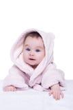 Nettes Babykind im rosa Bademantel, der sich auf Decke hinlegt Stockfoto