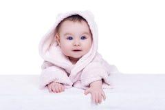 Nettes Babykind im rosa Bademantel, der sich auf Decke hinlegt Lizenzfreie Stockbilder