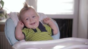 Nettes Babykind lacht und ausdehnend in den Küchenstuhl stock footage
