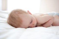 Nettes Babysleeping auf seinem Bauch Stockbilder