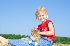 Nettes Bauernhofmädchen in den Flechten und in der Holding eine Katze. Stockfotos