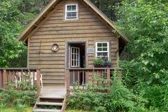 Nettes Blockhaus im Wald in Alaska Portal in der Front mit der Tür offen stockfoto