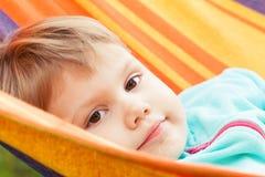 Nettes blondes Baby, das in gestreifter Hängematte liegt Lizenzfreies Stockfoto