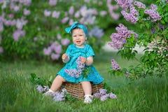 Nettes blondes Baby, das Zeit auf einem ehrfürchtigen Platz zwischen lila Spritzenbusch genießt Junge Dame mit dem Korb, der von  Stockfotografie