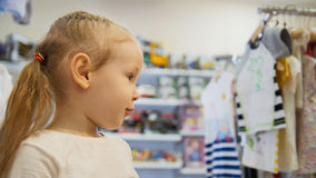 Nettes blondes Baby im Kinderkleiderspeicher Lizenzfreie Stockfotografie