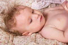 Nettes blondes Baby mit den schönen blauen Augen, die auf Bett mit Spielzeug liegen Stockfotografie