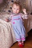 Nettes blondes Baby mit den schönen blauen Augen, die mit Spielzeug sitzen und lächeln Lizenzfreie Stockbilder