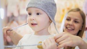 Nettes blondes Baby mit der Mutter, die das Einkaufen - kaufenden Hut tut Stockfotografie