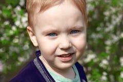 Nettes blondes Baby mit hellem Lächeln der blauen Augen im Blütenpark Gefühl des Glückes, Spaß, Freude lizenzfreie stockbilder