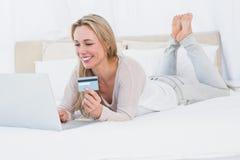 Nettes blondes Einkaufen online auf dem Bett Stockfotografie