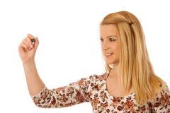 Nettes blondes Frauenschreiben auf leerem transparentem Brett mit einem marke Lizenzfreie Stockfotos