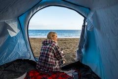 Nettes blondes Gebrauchstelefon am Kampieren im Windstrand Lizenzfreie Stockfotografie