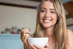 Nettes blondes, Getreide zum Frühstück essend Stockfotografie
