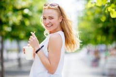 Nettes blondes haltenes Milchshake und darstellen Zunge Stockfotografie
