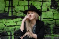 Nettes blondes jugendlich gegen Steinwand mit grünen Graffiti Stockfoto