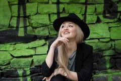 Nettes blondes jugendlich gegen Steinwand mit grünen Graffiti Stockfotografie