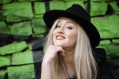 Nettes blondes jugendlich gegen Steinwand mit grünen Graffiti Stockbilder