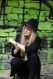 Nettes blondes jugendlich gegen Steinwand mit grünen Graffiti Stockbild