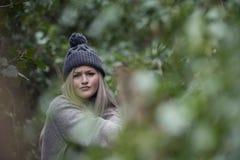 Nettes blondes jugendlich mit den netten Zahlen, die auf Bretterzaun sich lehnen Stockfotografie