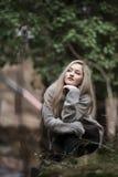 Nettes blondes jugendlich mit netten Zahlen am Wald Lizenzfreie Stockfotografie