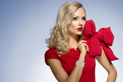 Nettes blondes junges Mädchen im Rot mit großem Bogen Stockbild