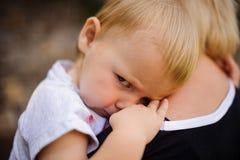 Nettes blondes Kind, das auf Mutter ` s Schulter liegt Lizenzfreies Stockfoto