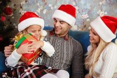 Nettes blondes Kind umarmt ihr Weihnachtsgeschenk beim Sitzen auf b Lizenzfreies Stockfoto