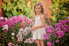 Nettes blondes Kindermädchen, das in blühendem Garten des Sommers spielt Stockbild