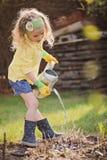 Nettes blondes Kindermädchen, das den Spaß spielt kleinen Gärtner hat Lizenzfreies Stockfoto