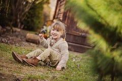 Nettes blondes Kindermädchen, das Spaß im Vorfrühlingsgarten hat Stockbilder