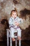 Nettes blondes kleines Mädchen, das auf weißem Stuhl sitzt stockbild