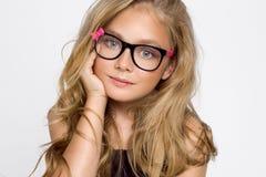 Nettes blondes kleines Mädchen in den Gläsern auf einem weißen Hintergrund in Stockbild