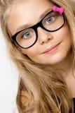 Nettes blondes kleines Mädchen in den Gläsern auf einem weißen Hintergrund in Stockfotos