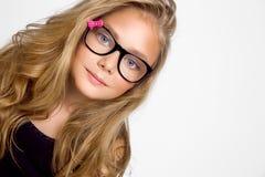 Nettes blondes kleines Mädchen in den Gläsern auf einem weißen Hintergrund in Lizenzfreies Stockfoto