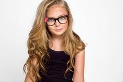 Nettes blondes kleines Mädchen in den Gläsern auf einem weißen Hintergrund in Lizenzfreie Stockfotografie