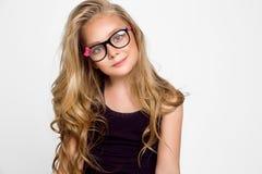 Nettes blondes kleines Mädchen in den Gläsern auf einem weißen Hintergrund in Lizenzfreie Stockfotos