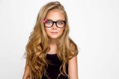 Nettes blondes kleines Mädchen in den Gläsern auf einem weißen Hintergrund in Stockfoto