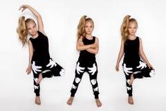 Nettes blondes kleines Mädchen in der Sportausstattung auf einem weißen Hintergrund im Studio Lizenzfreie Stockfotos