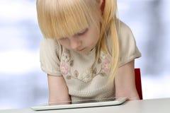 Nettes blondes kleines Mädchen mit digitaler Tablette Lizenzfreies Stockbild