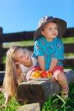 Nettes blondes kleines Mädchen und Junge, die mit Früchten spielt Stockbild