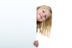 Nettes blondes Mädchen, das ein leeres Zeichen hält Lizenzfreie Stockfotos