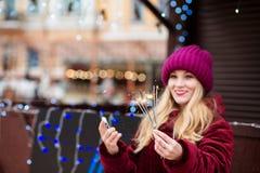 Nettes blondes Mädchen, das glühende Bengal-Lichter beim Christus hält Lizenzfreie Stockfotos