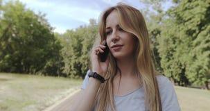 Nettes blondes Mädchen, das am Handy im Park spricht stock footage