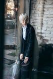 Nettes blondes Mädchen, das im modernen Café verwirrt schaut Lizenzfreie Stockbilder