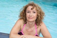 Nettes blondes Mädchen, das im Swimmingpool sich entspannt Stockfotografie