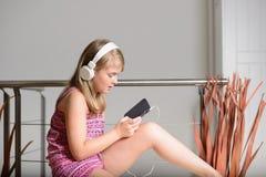 Nettes blondes Mädchen, das Musik hört Stockbild