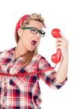 Nettes blondes Mädchen, das am Telefon schreit Stockfoto